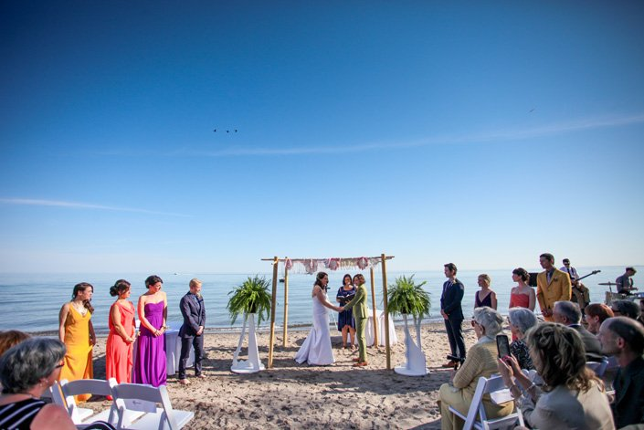 bride and groom take their vows under an arbor on the beach overlooking the lake